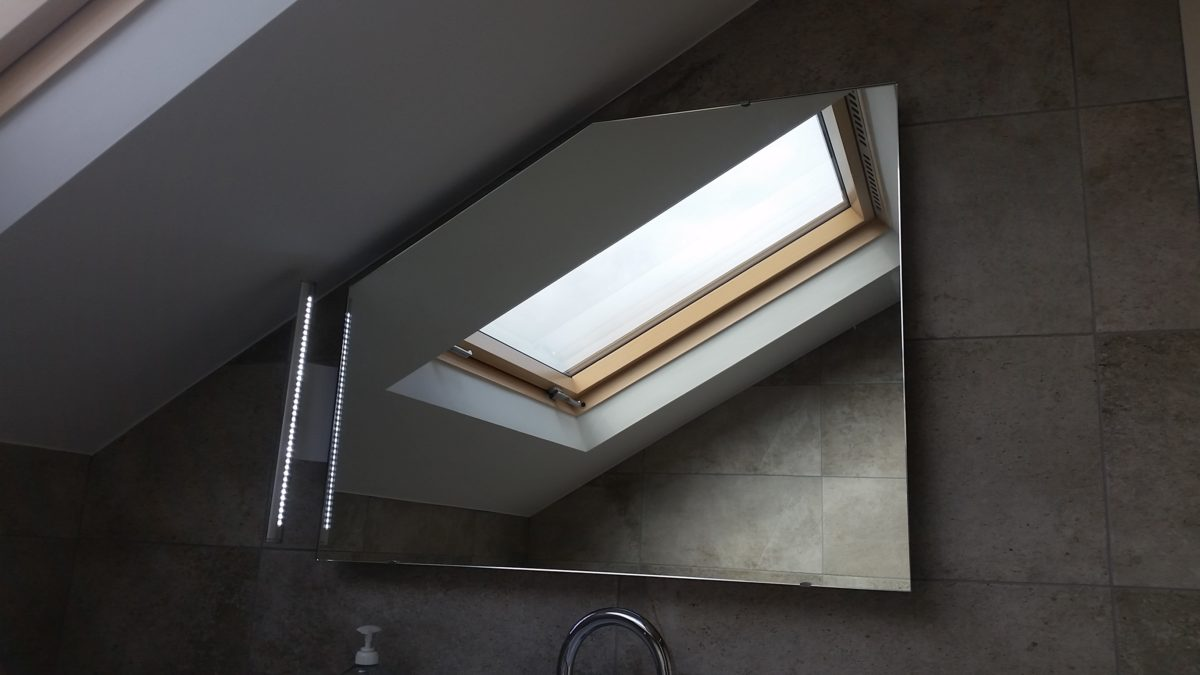Shaped mirror with steam demister and side light for attic bathroom
